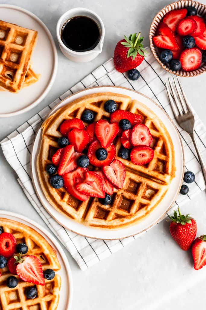 classic buttermilk waffle topped with berries on a plate next to a bowl of berries and container of syrup