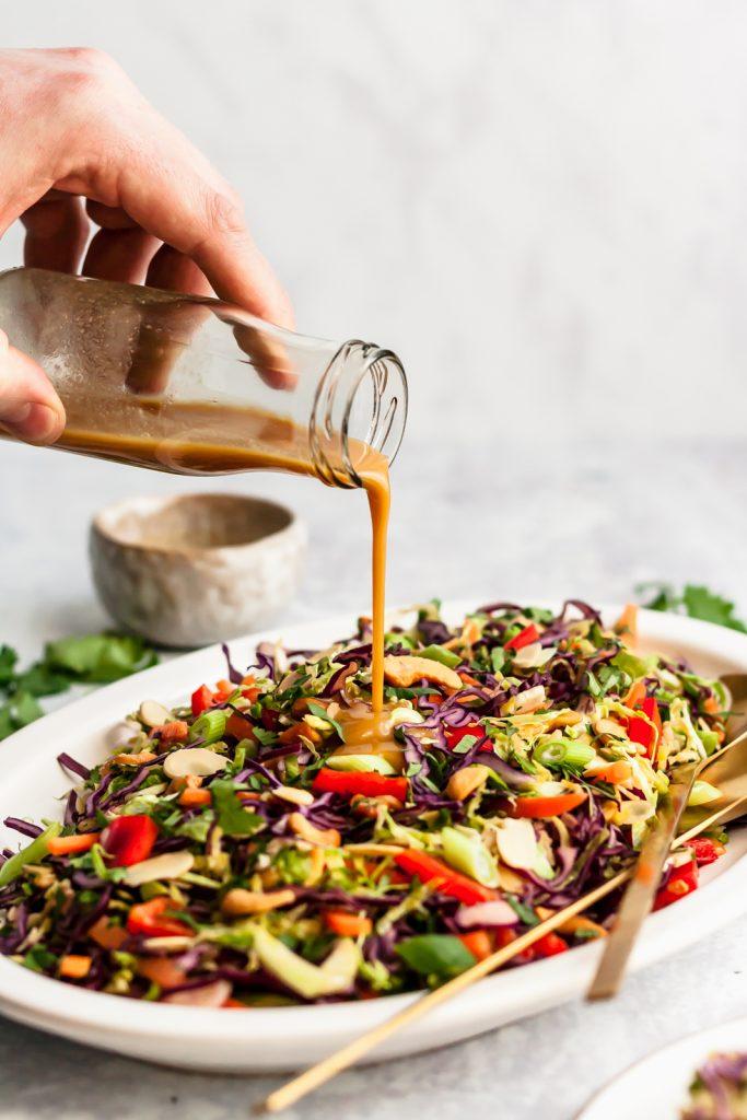 sesame ginger salad dressing being poured on top of salad