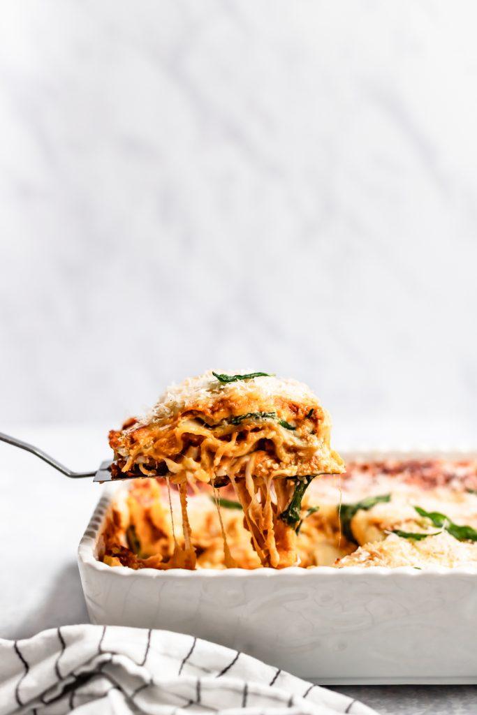 lifting a slice of vegetarian pumpkin lasagna out of a pan