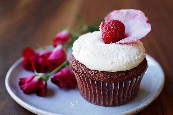 Macrina Bakerys red velvet Cupid Cupcake is filled with vanilla bean pastry cream and topped with buttercream, sugar, a raspberry, and a sugared rose petal.