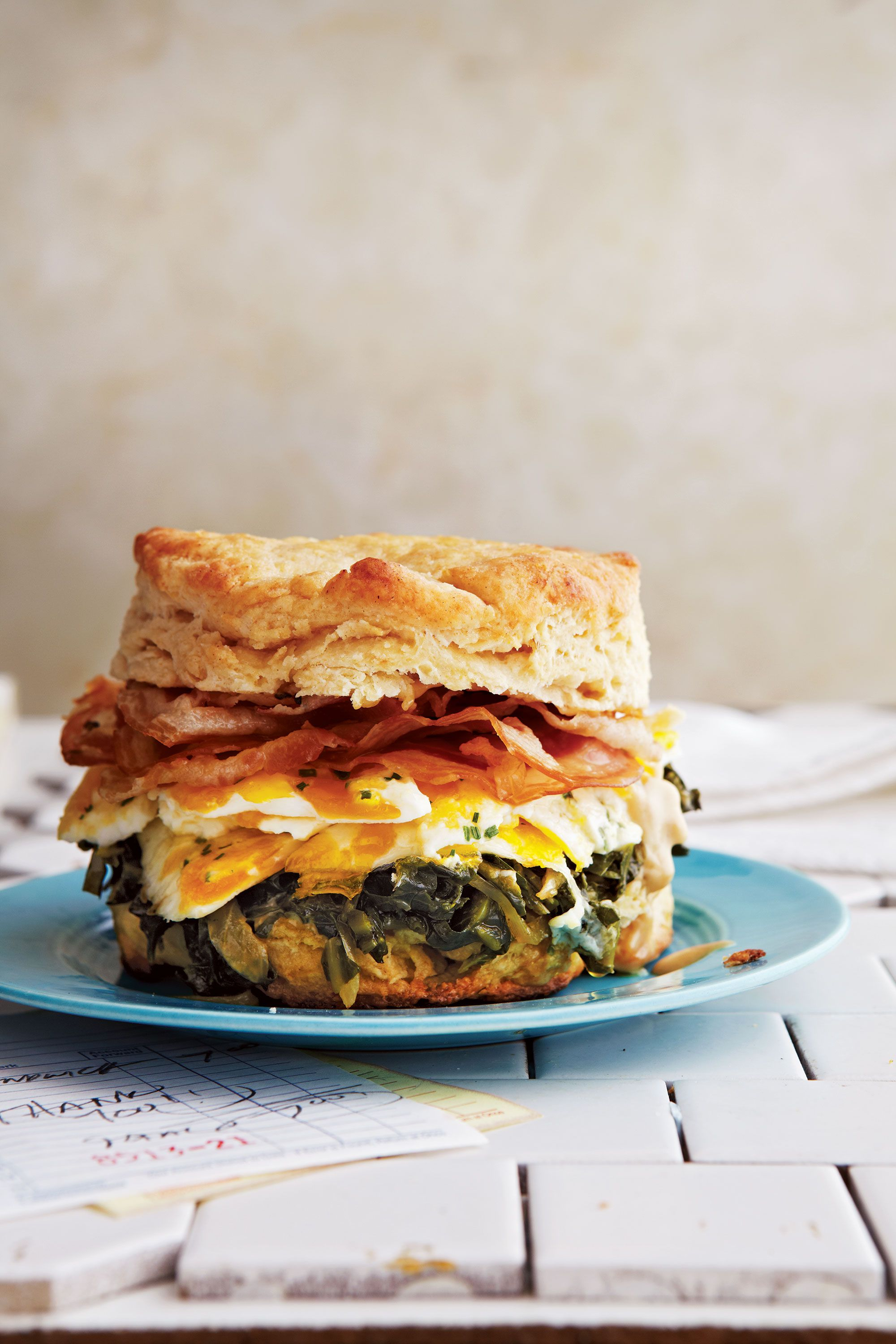 """Alvin Cailan of Los Angeles' cultish Eggslut goes pancetta-crazy in this sandwich, using eight slices on top of his gorgeously marbleized egg and cooking the collard greens in pancetta fat. Get the recipe for <a href=""""https://www.saveur.com/article/recipes/biscuits-with-pancetta-collard-greens-marbleized-eggs-and-espresso-aioli/"""">Biscuits with Pancetta, Collard Greens, Marbleized Eggs, and Espresso Aïoli</a>"""