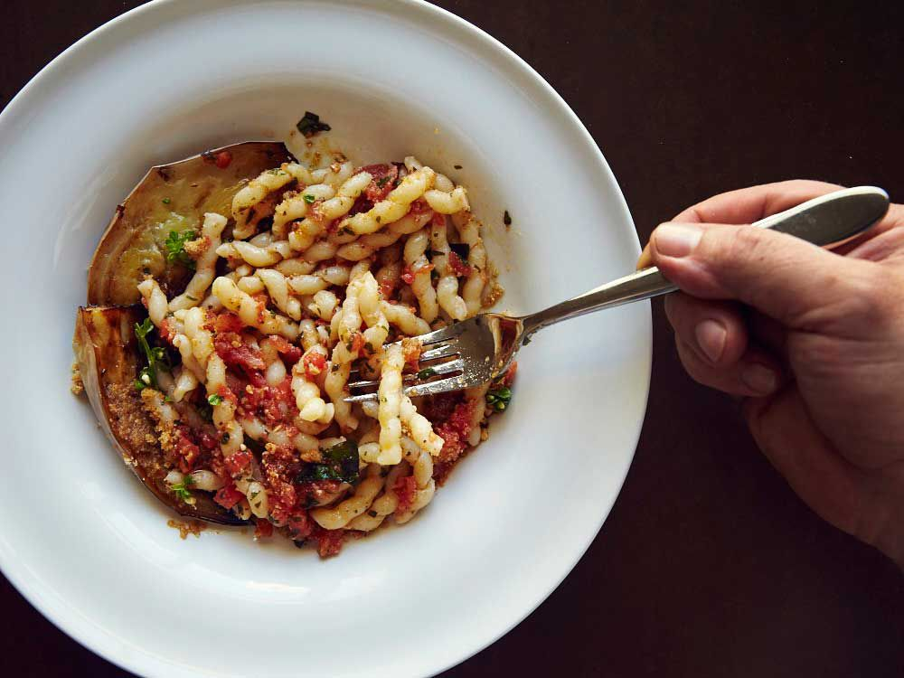 "The North African tradition of serving almonds in savory dishes is reflected in the pesto for this dish, in which the nuts are mixed with tomatoes and basil and tossed with <em>busiate</em>, the traditional corkscrew-shaped pasta from Trapani. Though we call for homemade pasta, you can substitute 12 ounces of dried <em>busiate</em>, or your favorite noodle. Get the recipe for <a href=""http://www.saveur.com/sicilian-almond-pesto-eggplant-pasta-recipe"">Corkscrew Pasta with Eggplant and Tomato-Basil Pesto (Busiate con Pesto alla Trapanese)</a>"