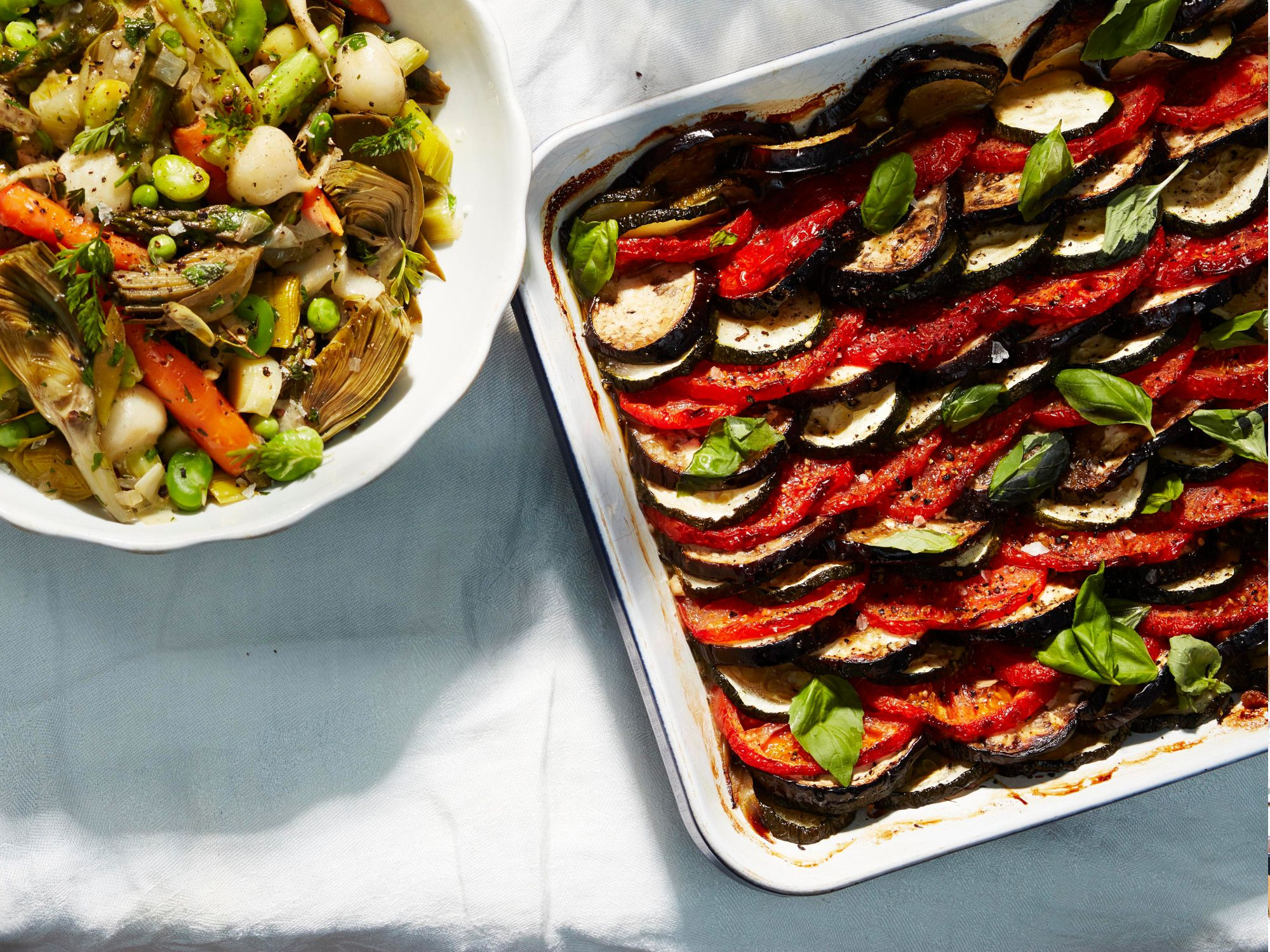 "A tian is a type of gratin, typically vegetables baked in an earthenware dish. (The word ""tian"" also refers to the earthenware dish itself.) This classic Provençal version is made with alternating rows of sliced zucchini, eggplant, and tomato. The flavors meld as the vegetables cook together, somewhat like ratatouille. Seasoned simply with thyme, garlic, and good fruity olive oil, the dish is best served at room temperature. Lulu insists it tastes even better made a day in advance. Get the recipe for <a href=""http://www.saveur.com/provencal-vegetable-gratin-tian-recipe"">Provençal Vegetable Tian</a>"