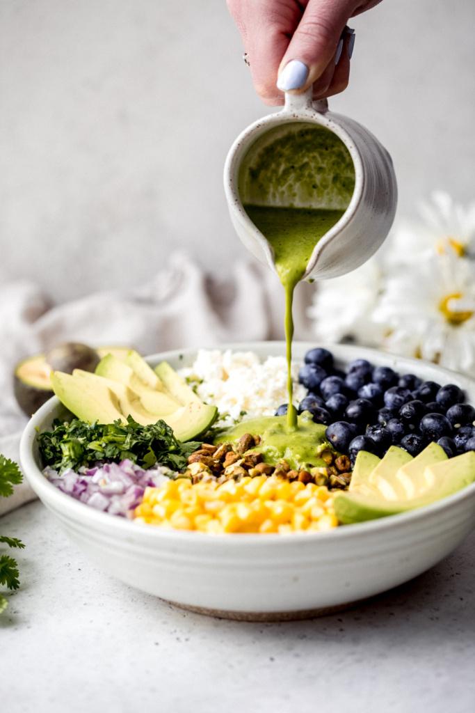 pouring homemade cilantro lime dressing onto a salad with corn, avocado, quinoa and blueberries