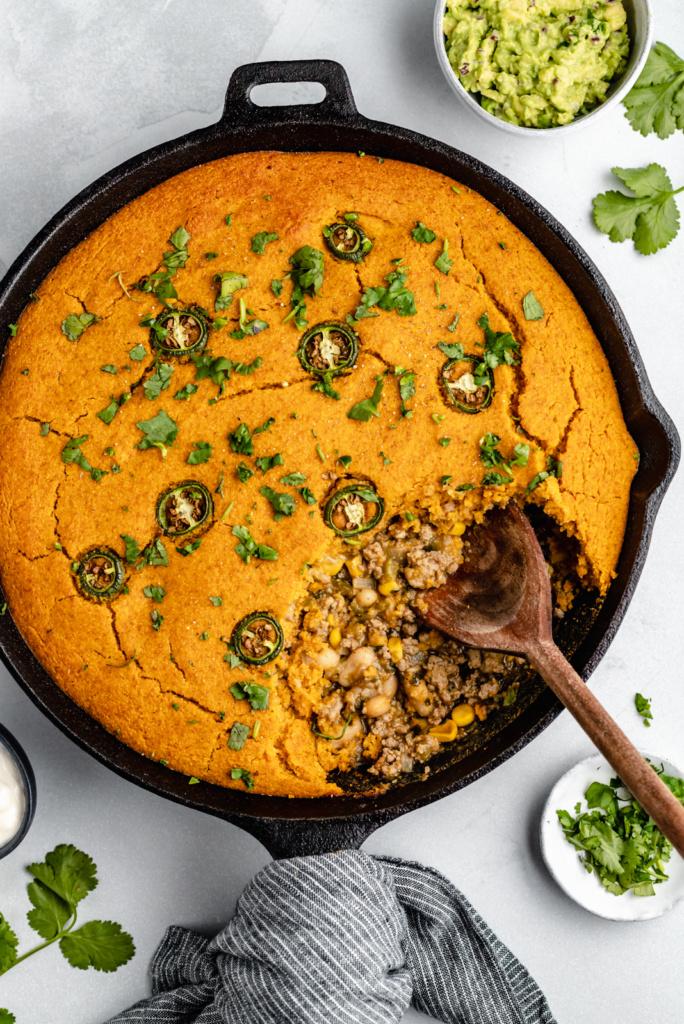 white chicken chili pie with pumpkin cornbread crust in a skillet