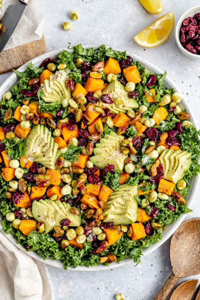 sweet potato kale salad in a bowl topped with avocado