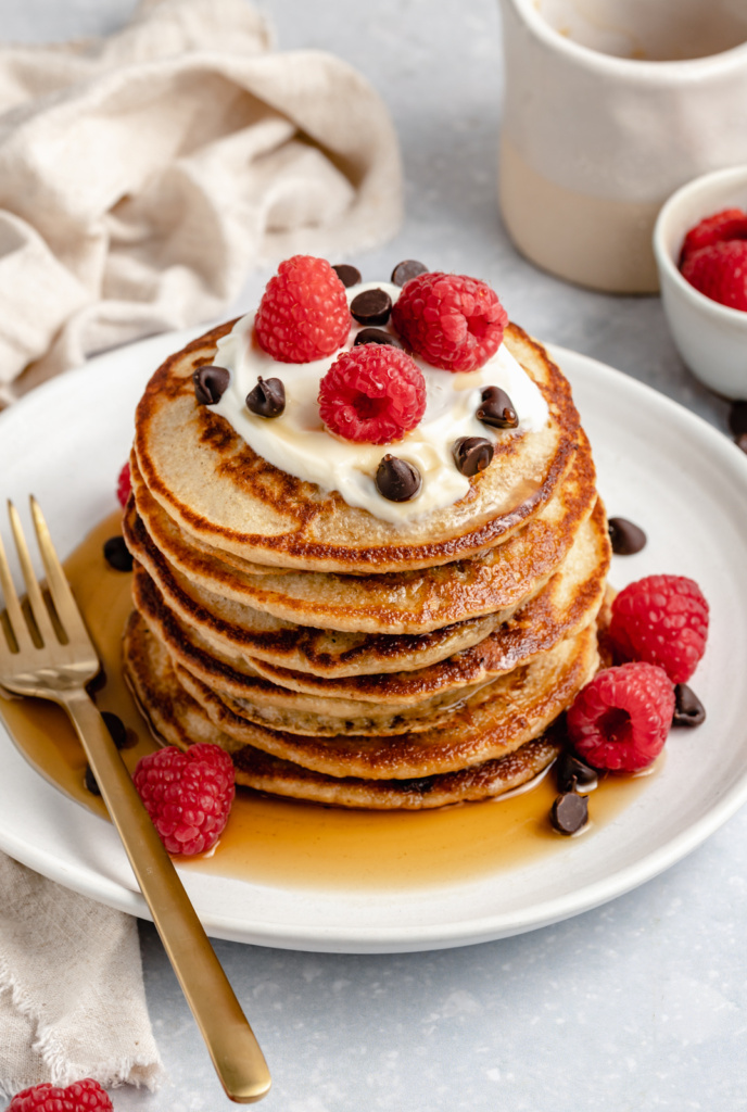 stack of gluten free yogurt pancakes topped with raspberries
