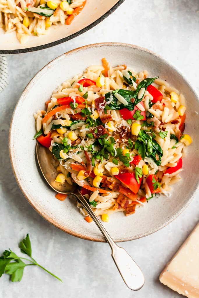 garlic parmesan orzo pasta in a bowl with veggies and a spoon