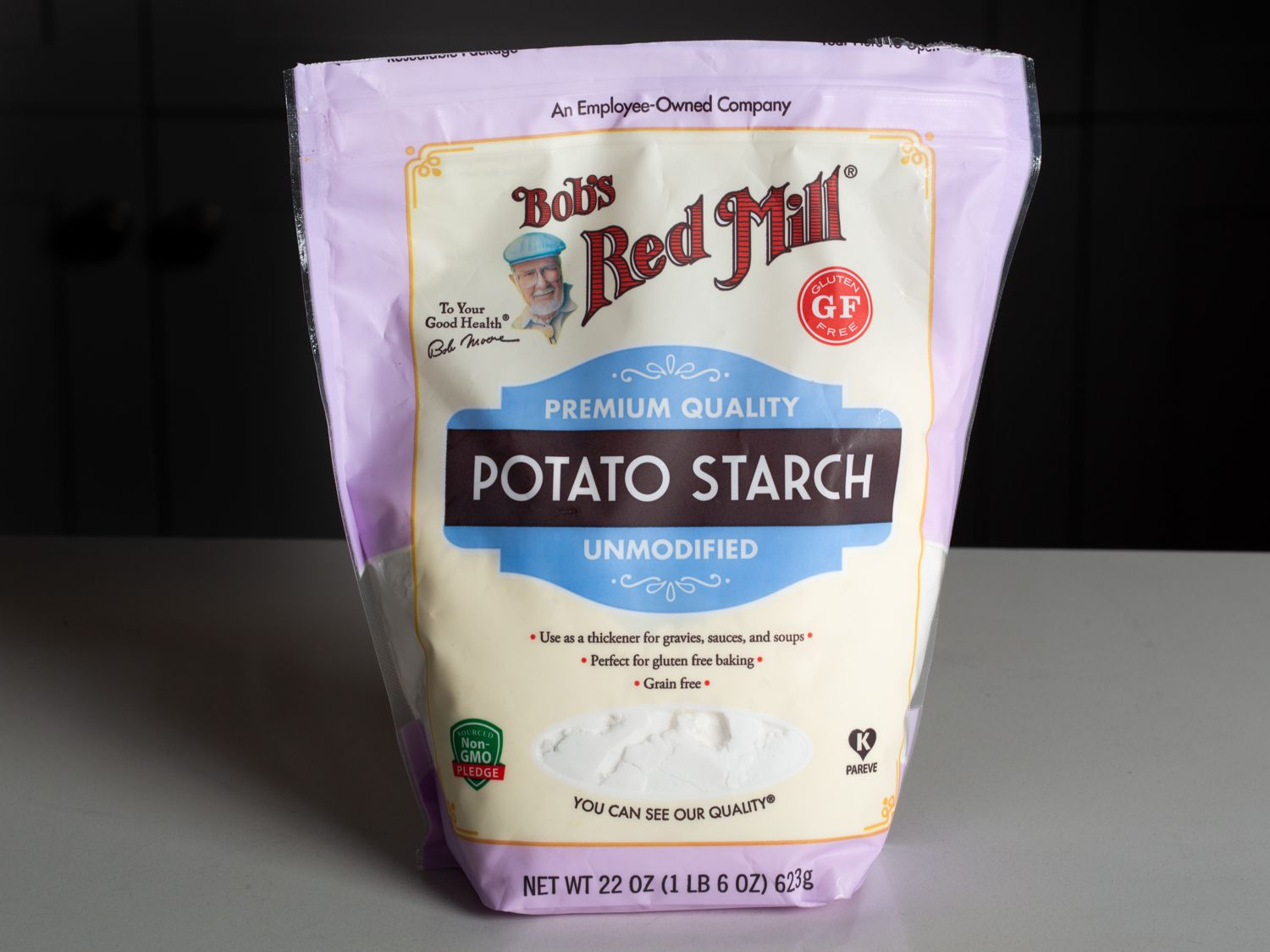 Bag of Bob's Red Mill Unmodified Potato Starch on a counter with a black background