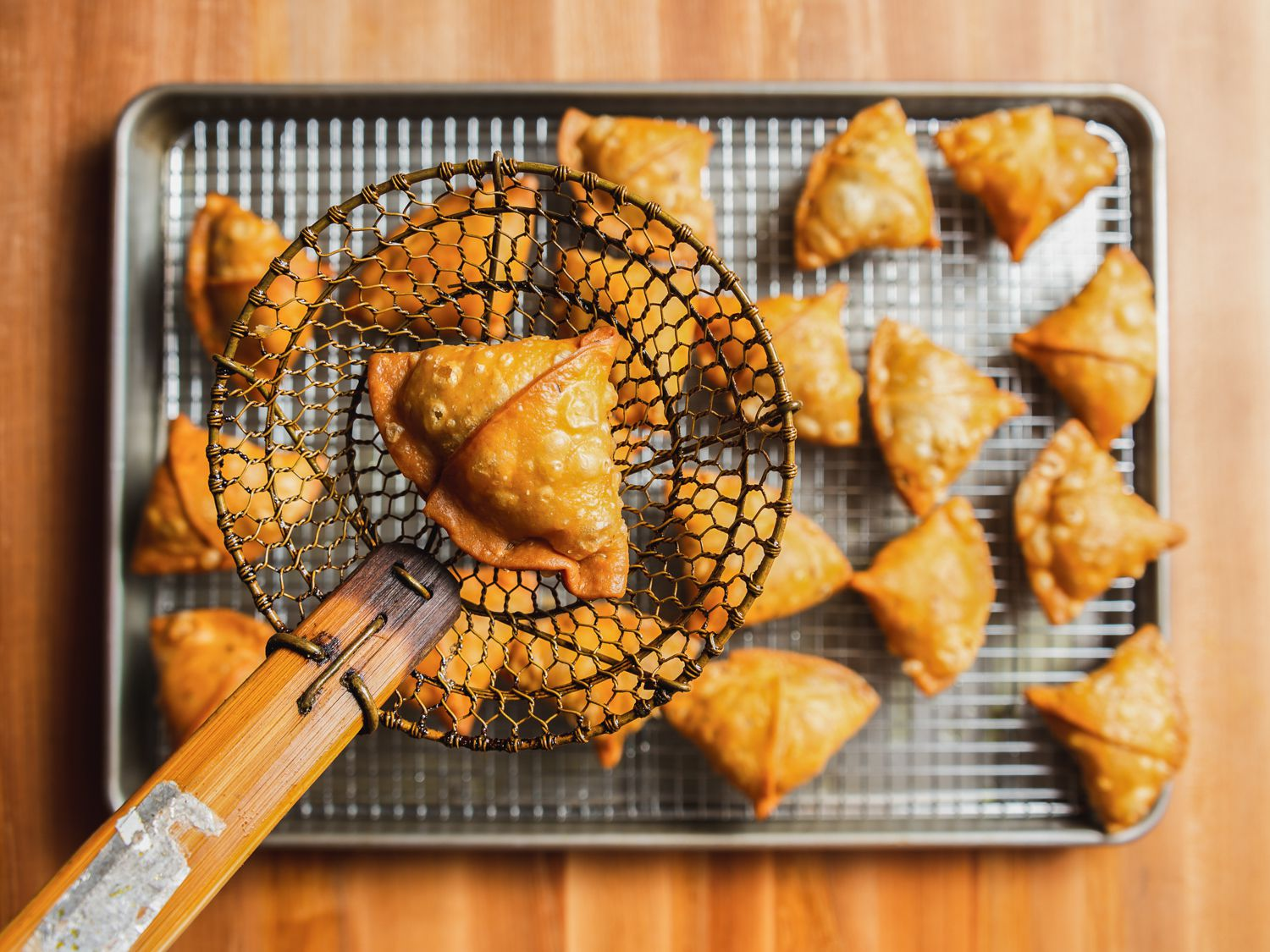 Fried samosa in a spider strainer held aloft a rimmed baking sheet with a wire rack set into it with samosas cooling on top