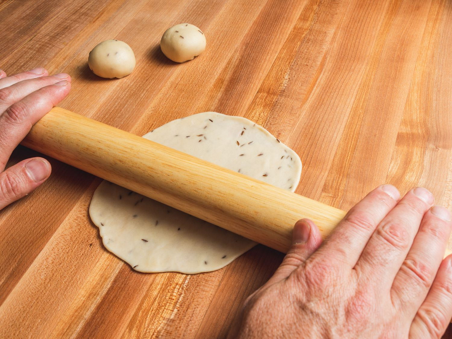 Samosa dough ball being rolled out with a rolling pin into a circle