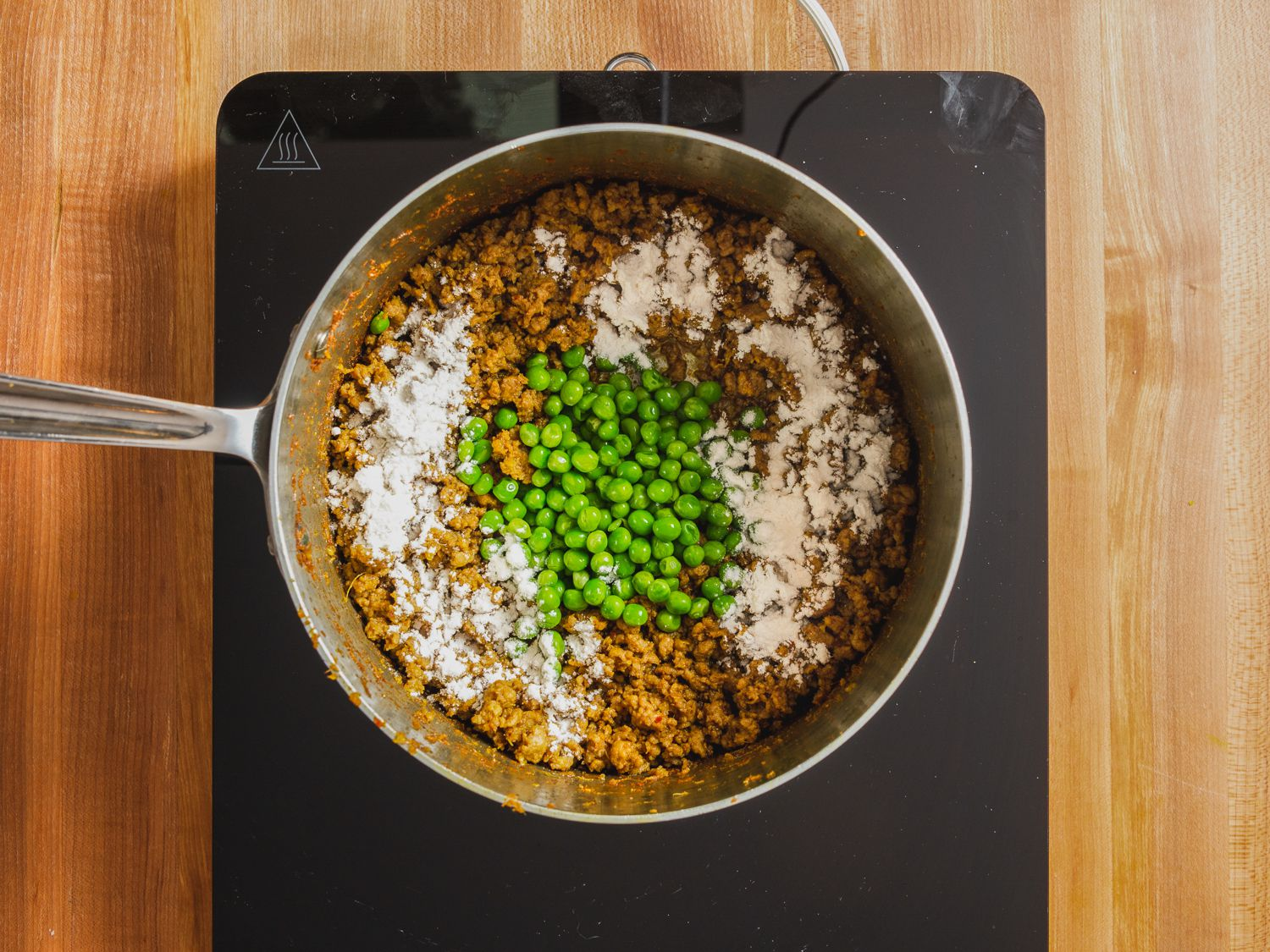 Overhead photo of peas and flour added on top of lamb kheema mixture in a saucepan