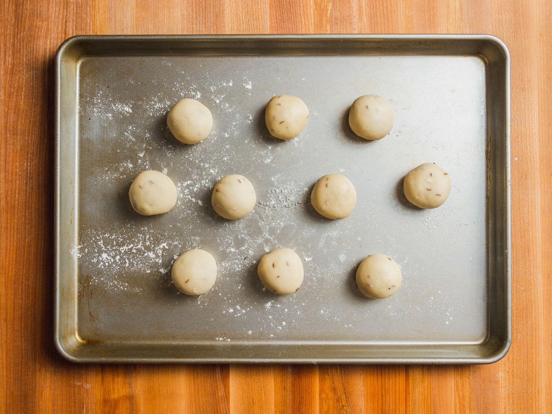 10 samosa pastry dough balls on a floured baking sheet