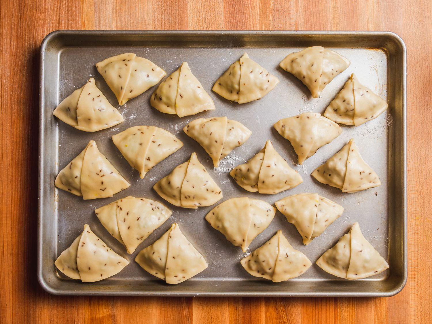 Wrapped samosas on a lightly floured baking sheet, ready for frying